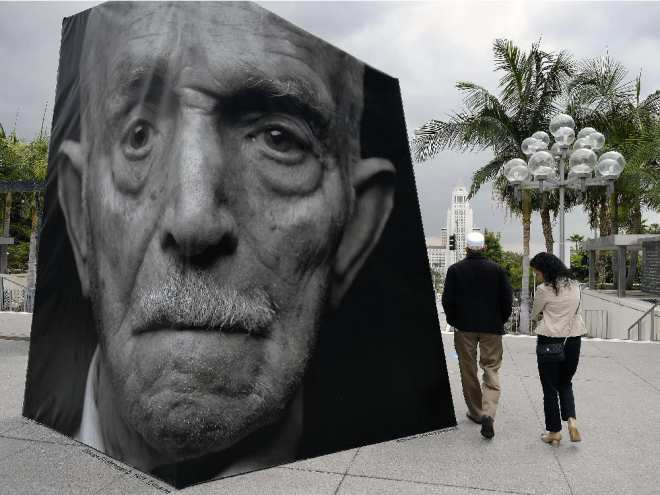 A couple walk past an outdoor installation called iwitness, a grouping of 20 larger-than-life 3-D photo sculptures of Armenian genocide survivors, at the Music Center Plaza in downtown Los Angeles on Friday, April 24, 2015.