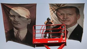FILE - In this Sunday, May 17, 2015 file photo, a Turkish police officer scans the area from a platform, backdropped by posters of Turkish Republic founder Mustafa Kemal Ataturk, left, and Turkey's current President Recep Tayyip Erdogan, right, during a political rally of AKP, The Justice and Development Party in Istanbul. After his party suffered major losses in June elections, Erdogan seems to be back in control and edging Turkey towards repeat elections, and gambling that a new ballot could revive his fortunes. (AP Photo/Lefteris Pitarakis, file)