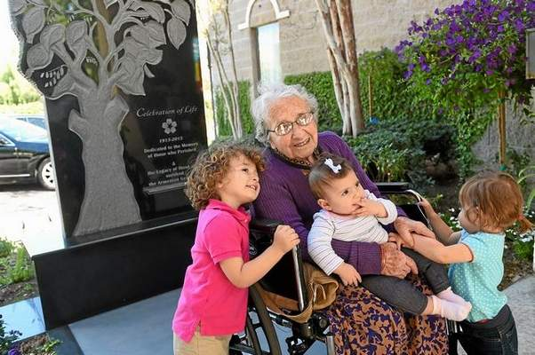Armenian Genocide survivor Yevnige Salibian poses for a photo with her great-grandchildren Vaughn Bahadarian, left, Aykienne Kiledjian and Brielle Bahadarian following a memorial service and the unveiling of a Armenian Genocide monument at the Ararat Home of Los Angeles on March 12, 2015. Salibian died Aug. 29, 2015 at the age of 101.