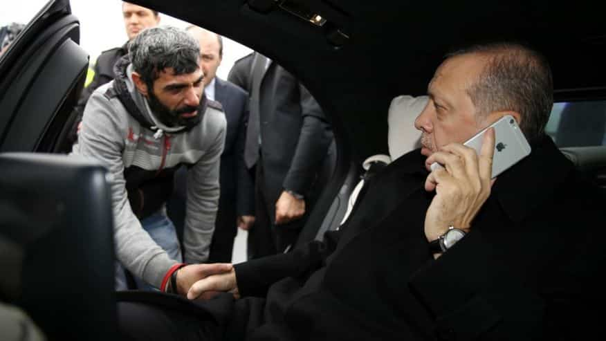 Dec. 25, 2015: Turkish President Recep Tayyip Erdogan, right, takes Vezir Cakras by hand while speaking on his mobile phone inside his car stationed over the Bosporus Bridge in Istanbul. (Yasin Bulbul, Presidential Press Service Pool via AP Photo)