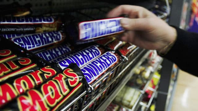 A customer picks up a Snickers Bar in a supermarket GETTY IMAGES