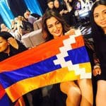 Iveta Mukuchyan displays the Artsakh flag during a Eurovision press conference
